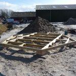Funderingsframe voor de kota geplaatst op een zandbed, hardhouten klossen en betontegels